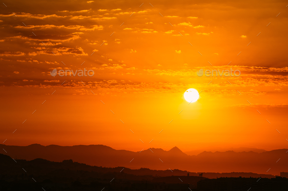Sunset Sunrise Over Dark Mountain Silhouette. Yellow And Orange - Stock Photo - Images