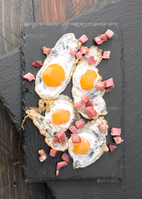 overhead shot fried quail egg with baked ham on black stone - Stock Photo - Images