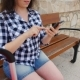 Young Woman Traveler Sits and Looks at Smartphone - VideoHive Item for Sale