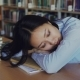 Young Beautiful Tired Asian Female Student Is Sitting at Desk with Her Head on It, She Is Sleeping - VideoHive Item for Sale