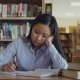 Young Asian Teenage Girl Is Sitting at Desk in Big Library Rewriting Text From Book. She Is Tired - VideoHive Item for Sale