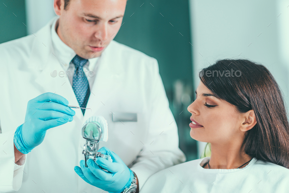 Dentist showing jaw model to patient - Stock Photo - Images