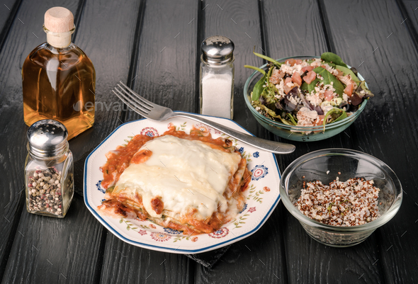 baked lasagna on black wooden board - Stock Photo - Images