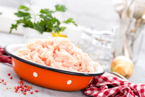 Forcemeat. Raw ground chicken meat in bowl on white kitchen table. Fresh minced chicken breast meat - Stock Photo - Images