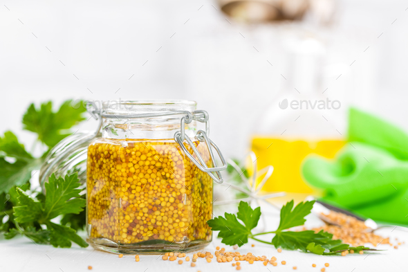 Mustard in glass jar on white wooden table closeup. Dijon mustard - Stock Photo - Images