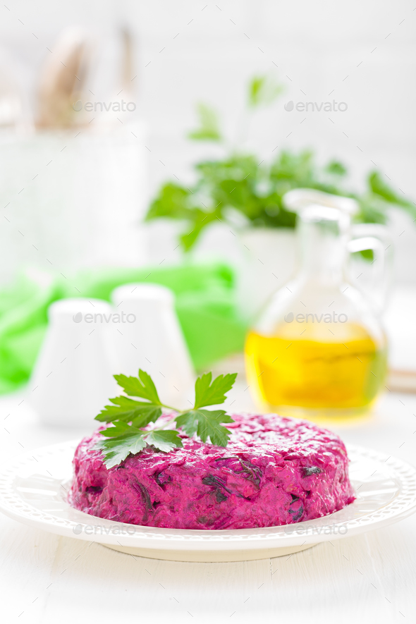 Salad of boiled beet. Beetroot salad with prune, walnuts and sour cream on white background - Stock Photo - Images