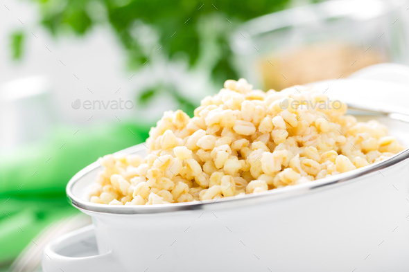 Bulgur wheat. Boiled bulgur cereal in pot on white kitchen table. Healthy vegetarian food - Stock Photo - Images