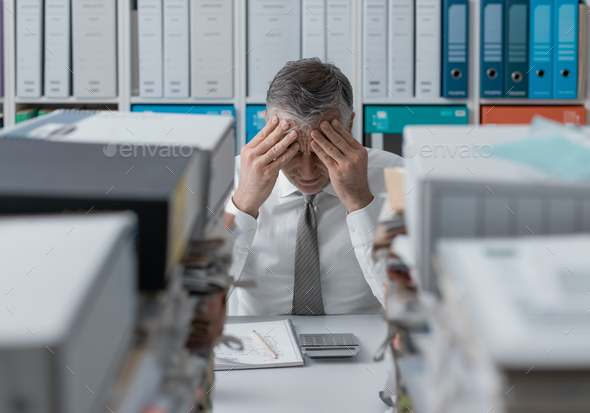 Stressed business executive and piles of paperwork - Stock Photo - Images