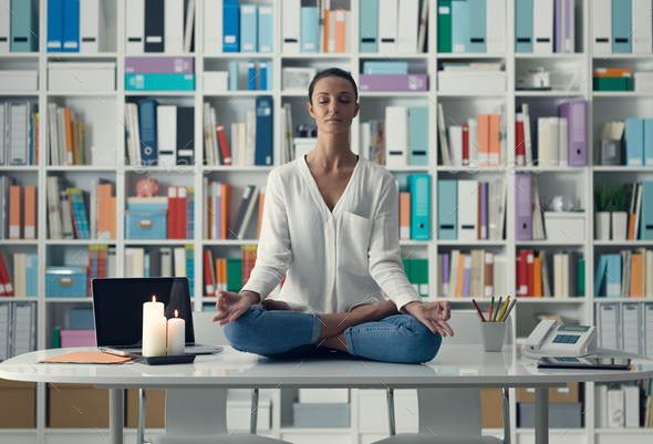 Woman practicing meditation on a desk - Stock Photo - Images