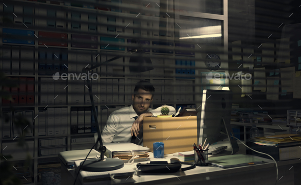 Fired office worker holding a box - Stock Photo - Images