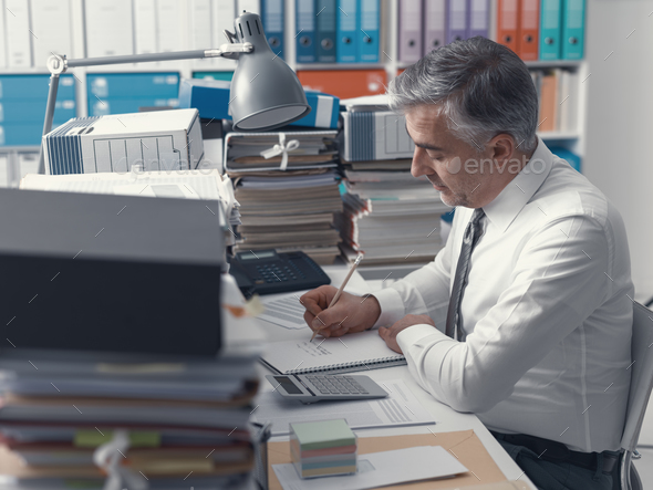 Businessman working in the office and piles of paperwork - Stock Photo - Images