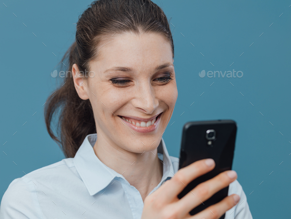 Smiling woman connecting with her smartphone - Stock Photo - Images