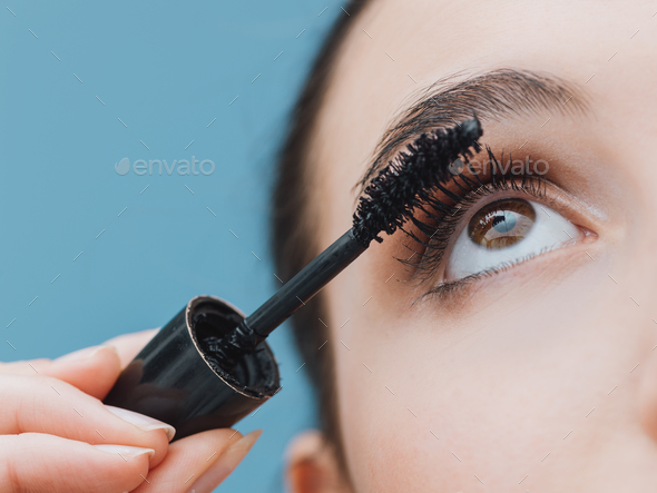 Woman applying mascara on her lashes - Stock Photo - Images