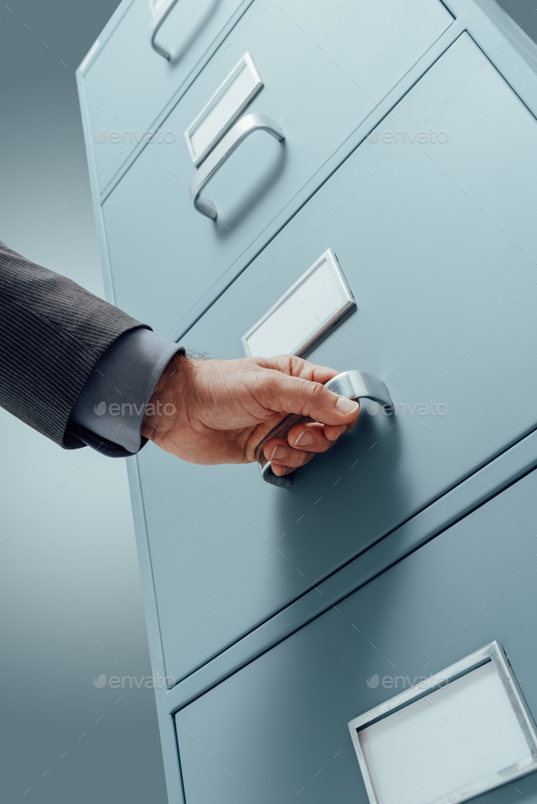 Office clerk searching files in the filing cabinet - Stock Photo - Images