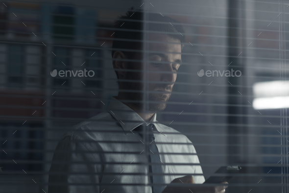 Corporate executive holding a smartphone - Stock Photo - Images
