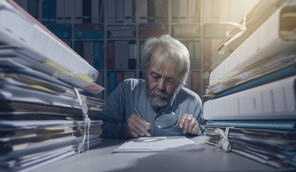 Senior researcher using a magnifier - Stock Photo - Images