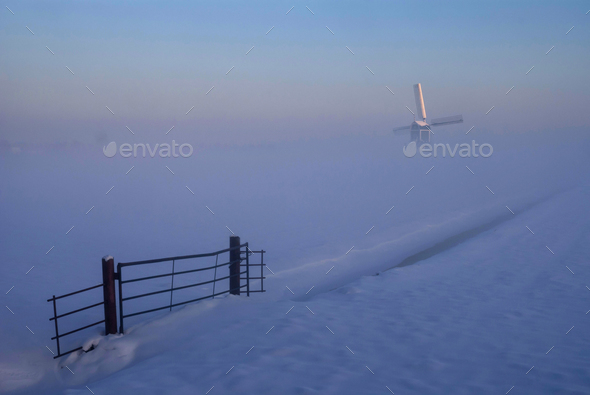 Windmill in a misty and wintry landscape - Stock Photo - Images