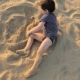 A Child Is Playing in the Sand on the Beach. - VideoHive Item for Sale
