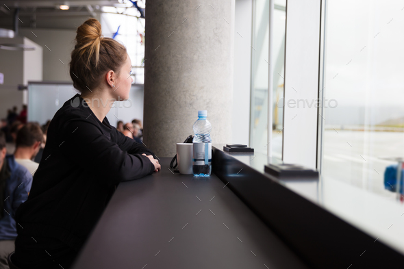 Traveling woman waiting at the airport and looking out the window - Stock Photo - Images