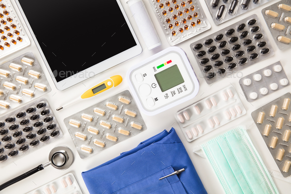 Pills By Blood Pressure Machine With Tablet Computer And Scrubs - Stock Photo - Images