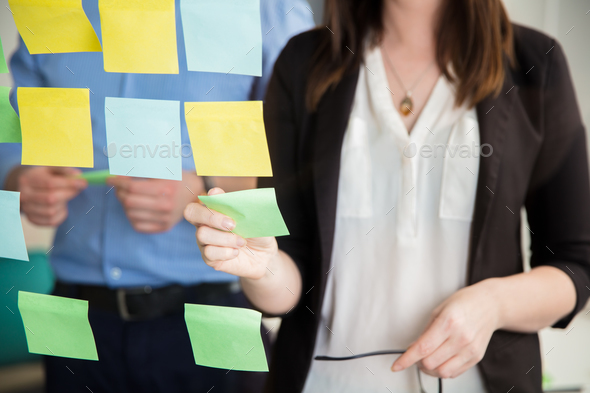 Midsection Of Businesswoman Sticking Note On Glass By Executive - Stock Photo - Images