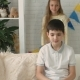 Girl Closes the Boy's Eyes While He Sits on the Sofa at Home - VideoHive Item for Sale