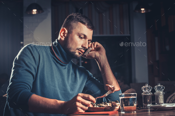 Man eating and speaking on mobile phone - Stock Photo - Images