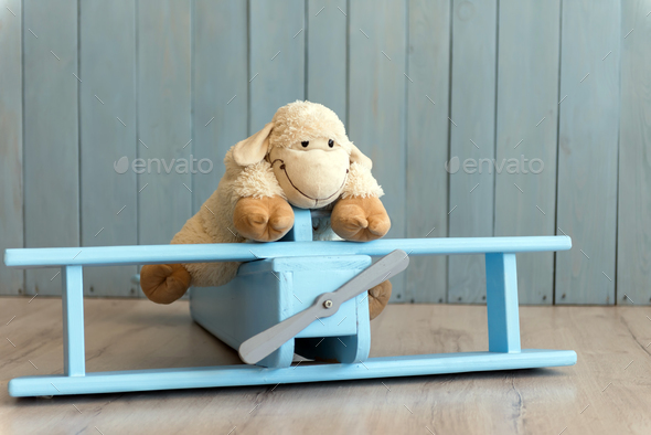 Wooden retro airplane model and sheep toy over retro vintage bro - Stock Photo - Images