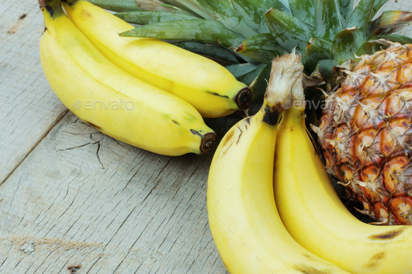 Banana and pineapple on wood - Stock Photo - Images