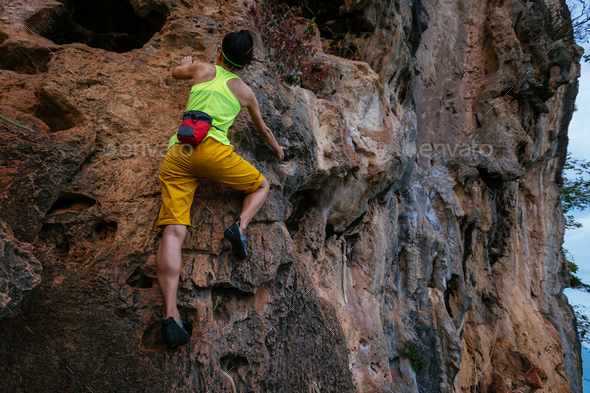 Woman climbing rock on cliff - Stock Photo - Images