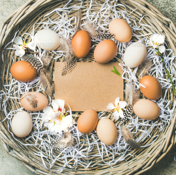 Natural colored eggs for Easter in basket over grey background - Stock Photo - Images