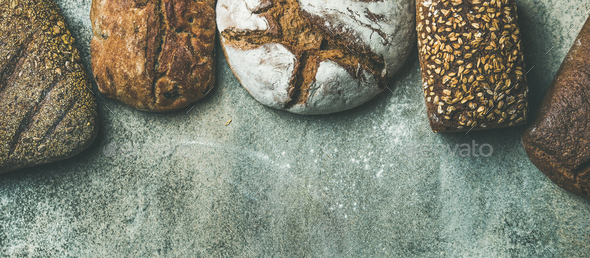 Top view of bread loaves over grey background, wide composition - Stock Photo - Images