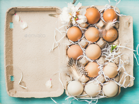 Natural colored eggs for Easter in box, blue background - Stock Photo - Images