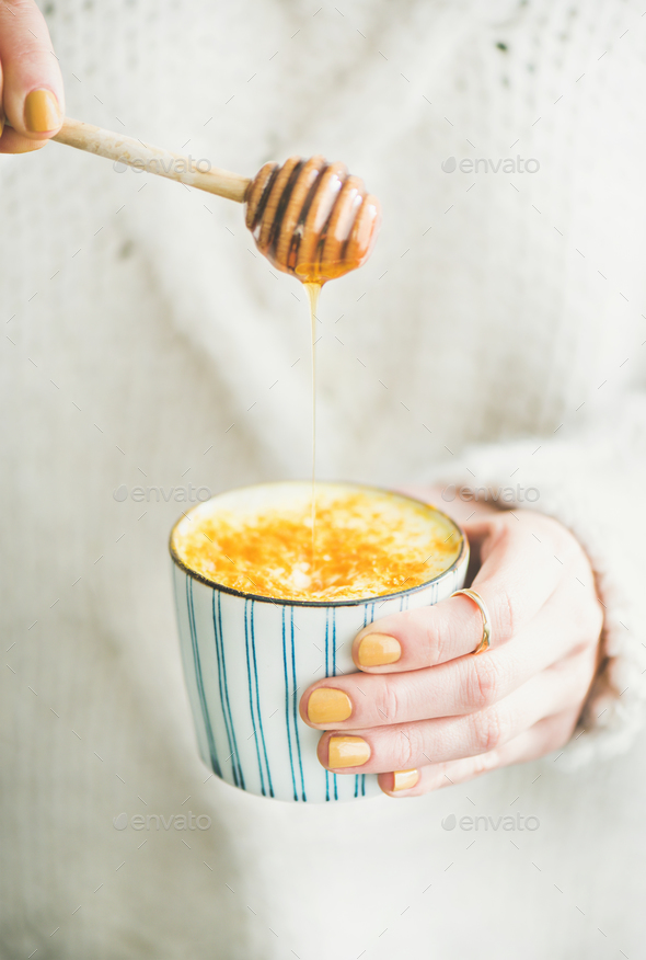 Turmeric latte, golden milk with honey in woman's hands, close-up - Stock Photo - Images