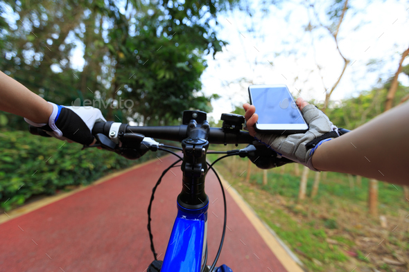 Cycling with mobile phone for navigation  - Stock Photo - Images