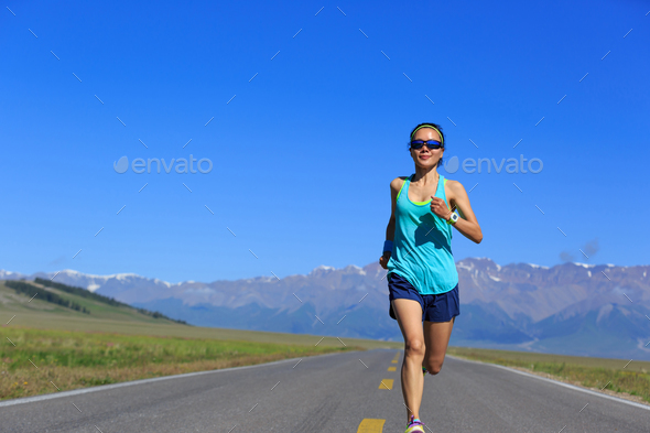 Fitness determined woman running on mountain trail - Stock Photo - Images