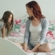 Little Cute Girl Giving Gift Box To Her Young Happy Mother Celebrating Birthday Sitting on Bed in - VideoHive Item for Sale