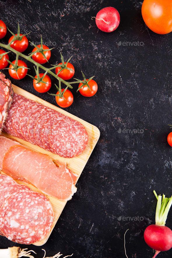Top view of antipasto appetizers next to cherry tomatoes - Stock Photo - Images