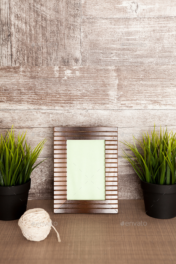 Beautiful photo frame next to two pots of grass - Stock Photo - Images