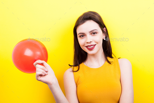 Happy woman playing with a red balloon - Stock Photo - Images
