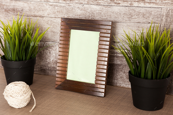 Vintage photo frame next to two pots of grass - Stock Photo - Images