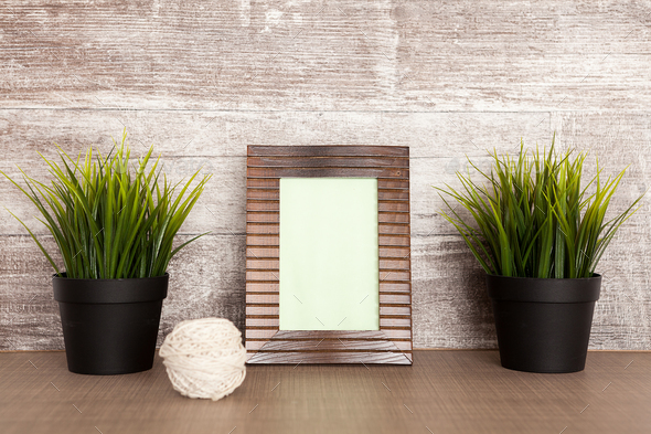 Old photo frame next to two pots with grass - Stock Photo - Images