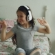 Smiling Cute Girl in Headphones Sitting in Bed and Dancing Funny at Home - VideoHive Item for Sale
