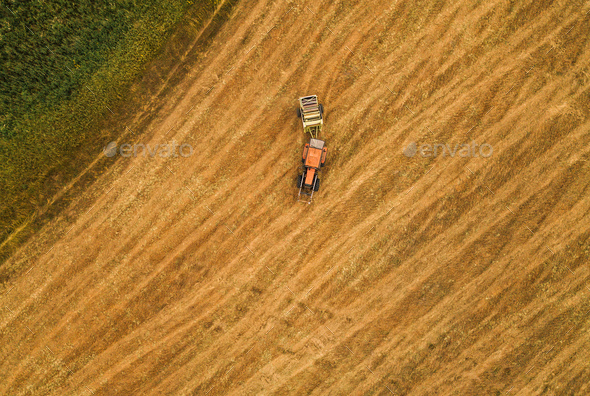 Aerial view of tractor making hay bale rolls in field - Stock Photo - Images