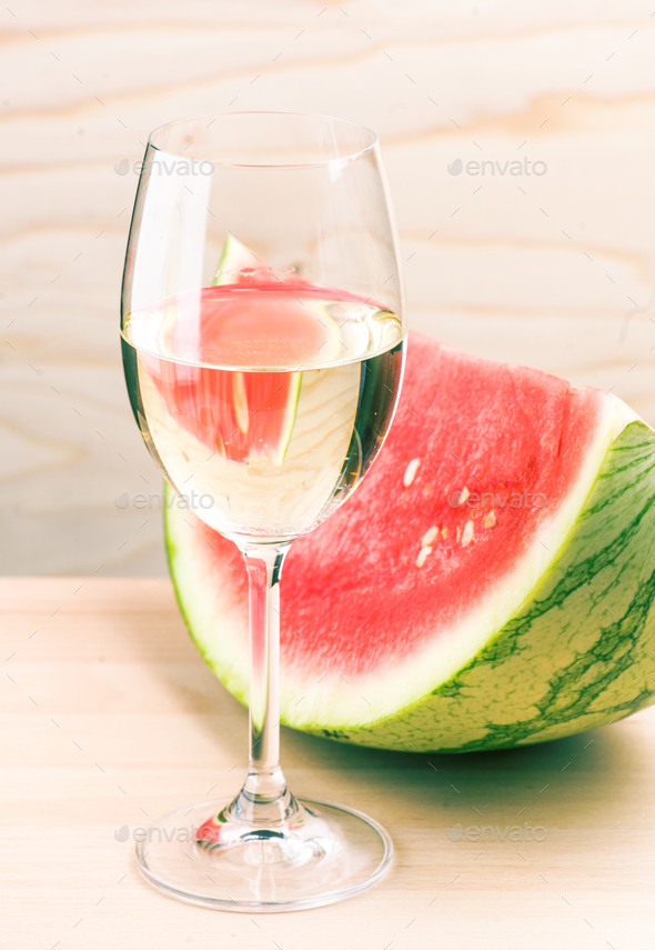 glass of white wine and watermelon on light wood - Stock Photo - Images