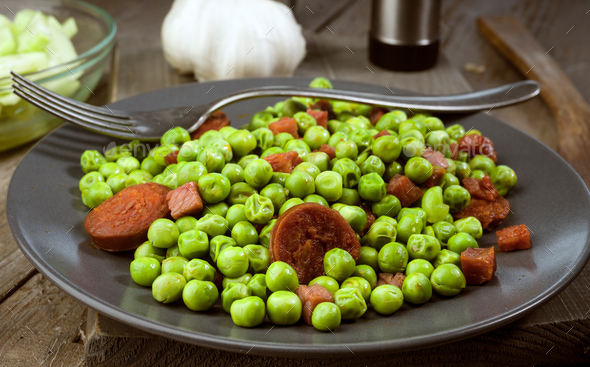 dish cooked with ham and chorizo peas in old wooden classic - Stock Photo - Images