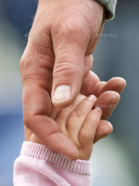 Child and parent holding hands - Stock Photo - Images