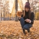 Young Beautiful Girl Collects a Bouquet of Fallen Leaves in Autumn Park - VideoHive Item for Sale