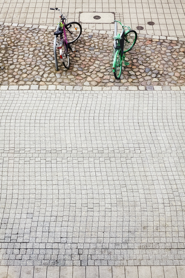Two bikes parked on cobblestone street pavement. - Stock Photo - Images