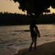 Girl with Surfboard Walking at Sunset - VideoHive Item for Sale